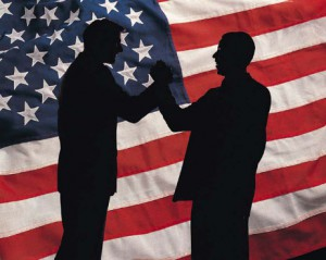 two men shaking hands in front of a us flag